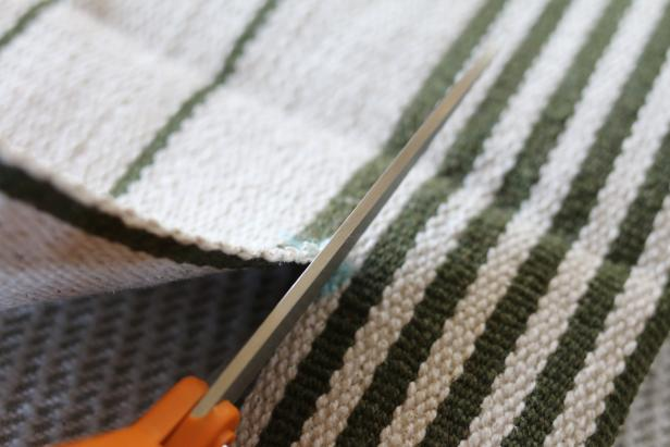 Use dressmaker shears to cut the third flat weave rug into four side panels for the slipcover. Two will be cut to the length of the pet bed and two will be cut to the width of the pet bed.