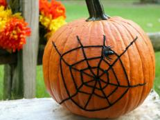 Pumpkin decorated with a spiderweb design for Halloween decor.