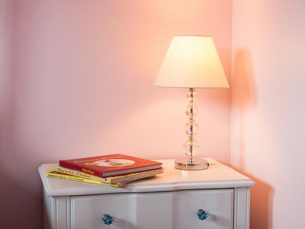 Glass Lamp on a White Bedside table in a Pink Girls Bedroom