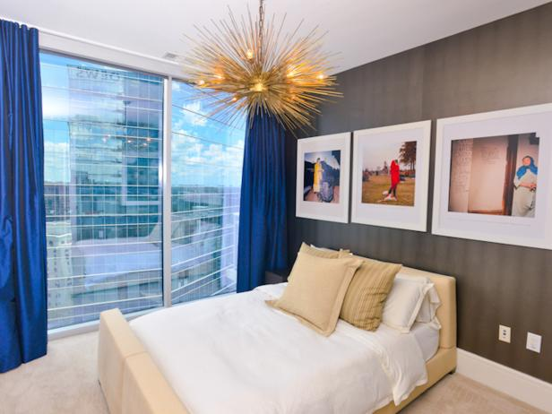 Trio of Photographs in High-rise Urban Bedroom with Modern Gold Chandelier