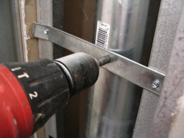 secure duct with metal straps between studs
