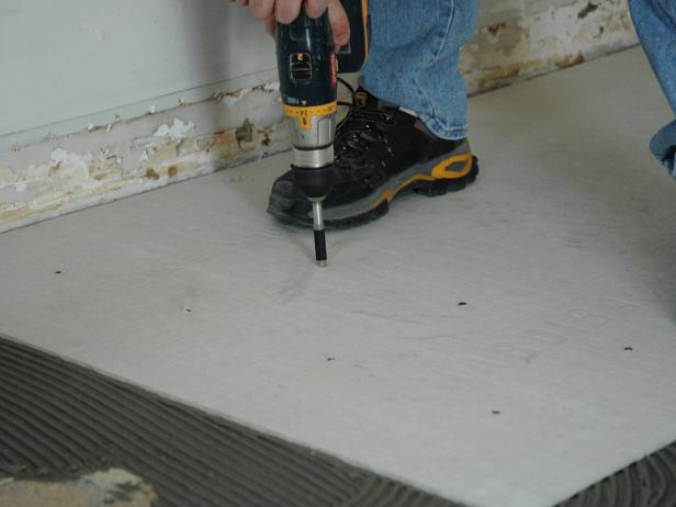 When the board is in the right place, begin screwing the backer board into the flooring below (Image 2).