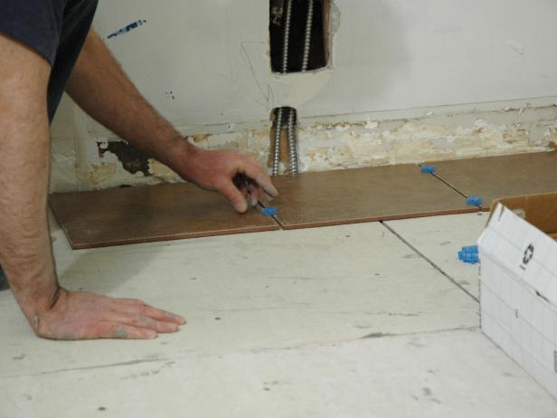 Using spacers as a guide, lay one row of tiles all the way across the floor and another row of tiles perpendicular to the first row (Image 1).