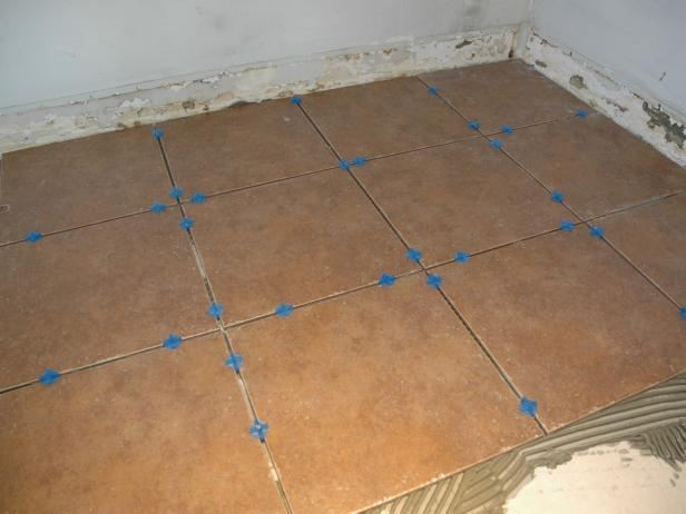 Lay the tiles down carefully and make any corrections and adjustments while the thinset is wet. Insert spacers to ensure each tile has the same size gap.