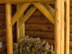 The firewood rack is faced with rough-hewn cedar logs and capped with metal roofing material.