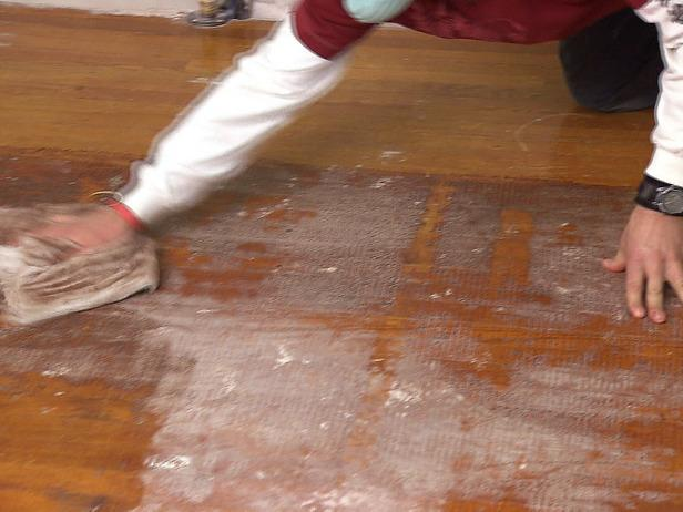 Man uses a rag to help a floor installation project using hardwood.