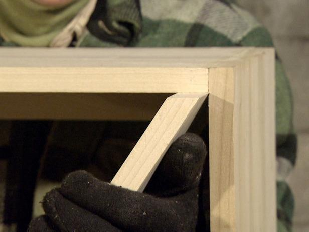 Close up of an angled shelf on a wine rack that is being constructed.