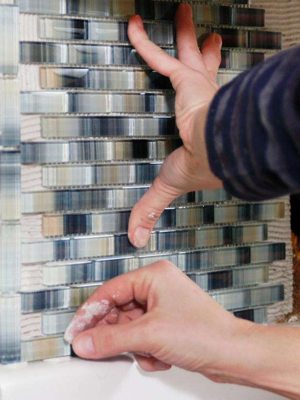 If you are installing sheets of smaller tile with mesh backing ,use a utility knife to cut the sheet to size. Press it firmly with your hands to secure on to wall.