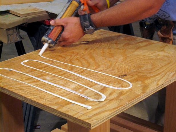Using a caulking gun to glue wood pieces together to form  the kitchen cart furniture project.
