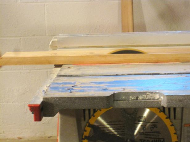 A saw cuts into the wood to construct a kitchen cart.