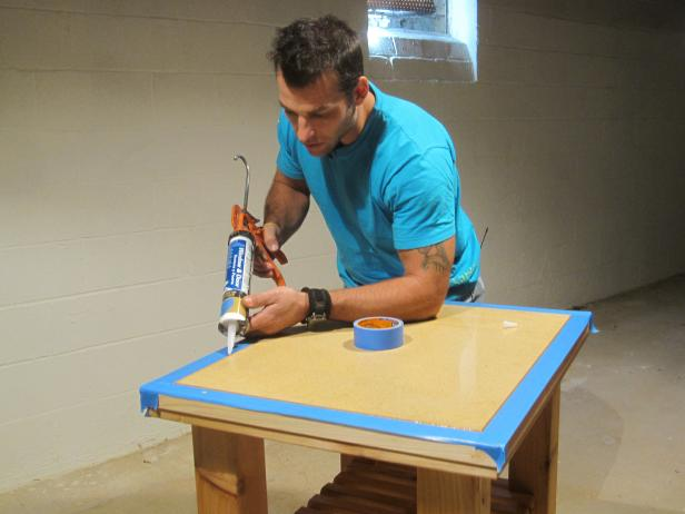 Marc adds silicone to the edges of the wood frame of the kitchen cart construction project.