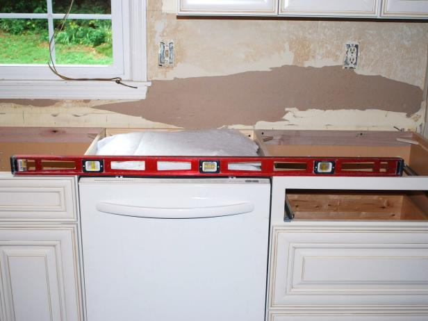 Check to make sure your base cabinets are level across their entire length. If not, unfasten the base units and level them with shims underneath the baseboard.