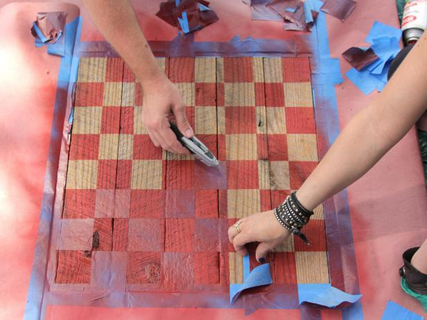 When the taped squares for the board are complete, spray-paint or brush paint the uncovered squares. Allow the surface to dry. Remove the tape to expose the checkerboard pattern on the rough table surface.