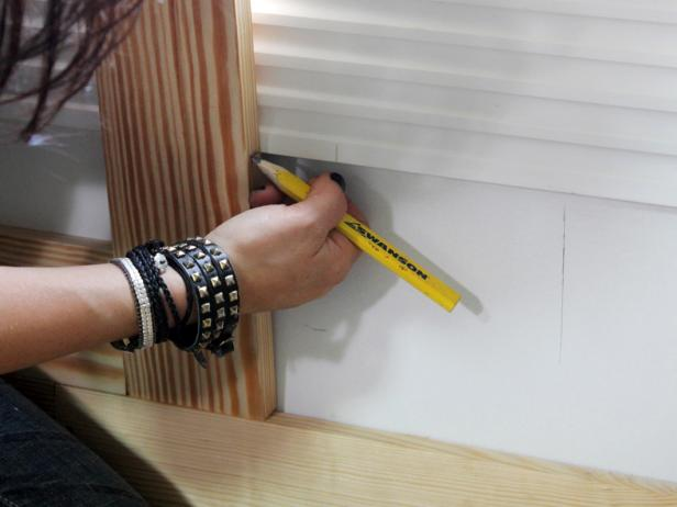 To cut a stile under the window, place a shortened length of stile atop the baseboard. Mark the stile where the cut will be made to fit the window trim. When cutting stiles around wall receptacles, use the pencil to outline the cut locations on the wall, then transfer the cut lines onto the stile.