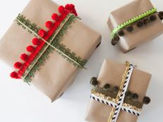 Wrap gifts with perfectly knotted pom-poms, sequins or lace and layer in any number of colorful combinations. It's as easy as wrapping with standard ribbon but is a fun, modern way to embellish kraft-paper-wrapped presents.