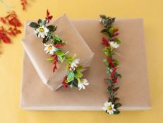 'Tis the season for holiday florals and, contrary to popular belief, your favorite blooms need not be confined to wreaths and fireplaces. This year, utilize your green thumb to craft small faux flower garlands to tie around gift boxes.