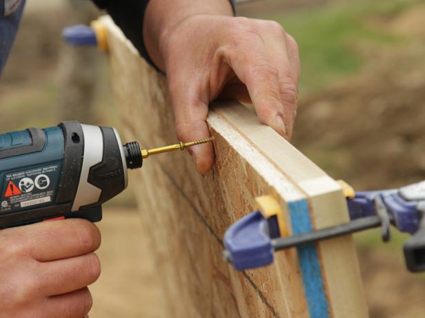 Driving the screws with the board face down or using two small clamps will help keep the trim from moving or pushing away from the sheathing while tightening.