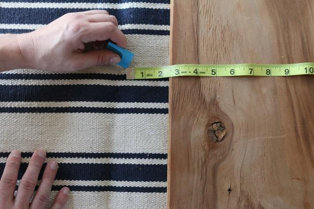 Place the cushion directly onto the flat weave rug. Use chalk to outline the chair cushion directly to the rug, allowing an additional 2 ½ inches all the way around to account for wrapping along the edges.