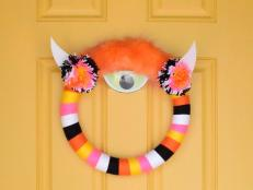 A standard wreath form is wrapped in yarn then adorned with horns and one giant eyeball to create an adorable way to greet trick-or-treaters.