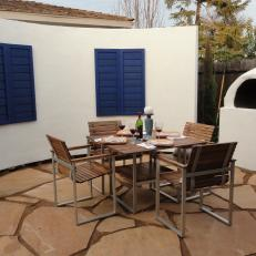 Outdoor Dining Area with a White Accent Wall